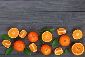 tangerine with leaves on black wooden background with copy space for your text. Flat lay, top view. Fruit composition
