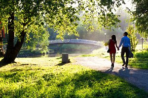 A pair of young people are walking in a sunny park holding hands
