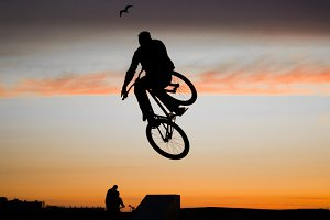 Cyclist jumping on a sunset