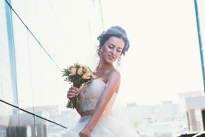 Bride and bouquet on backround mirror buildings.