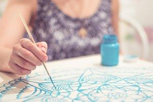 Asian girl draws at the mandala