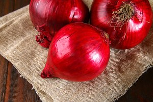 Fresh red onions on a wooden background.