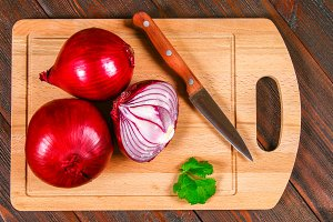 Fresh red onions and chopped slices on a wooden table. Top view.