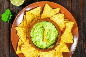 Traditional Mexican Guacamole sauce made from avocado and lime chips nachos on a brown wooden table. Top view.