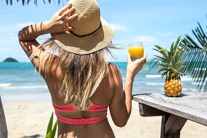 pretty girl in straw hat and bikini with summer drinks in hand, amid the palm trees and the beach