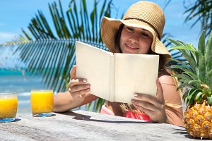 beautiful girl in a straw hat reading a book on a background of palm trees and summer drink with pineapple, on the beach