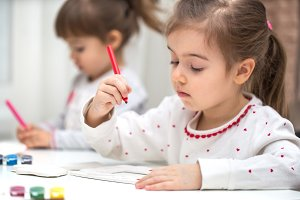 a little girl is engaged in creativity, draws with pencils and felt-tip pens