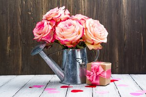 Beautiful pink rose in a tin watering can on wooden background