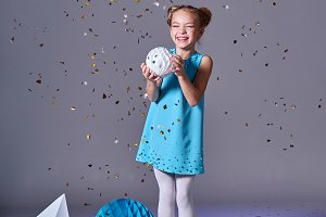 Cute baby girl in blue dress pretty model enjoying holiday and throwing confetti. Fashion kid christmas photos.