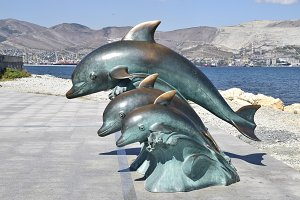 The bronze sculpture of three dolphins on the beach