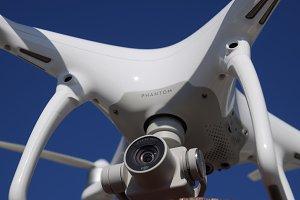 Quadrocopter DJI Phantom 4 against the blue sky.