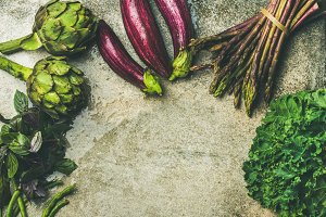 Flat-lay of green and purple raw vegetables over grey background