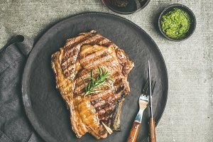 Flat-lay of Grilled rib-eye beef steak on bone, copy space