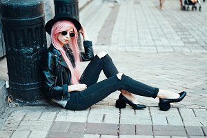 girl with pink hair posing on city street