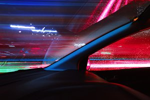 Night driving.Long exposure photo.City colorful night lights perspective blurred by high speed of the car.