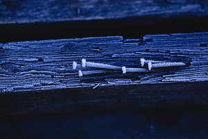 Frozen wooden surface with nails covered by ice crystals, macro photo.