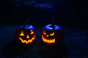 Two Halloween pumpkin in a mystical forest at night.