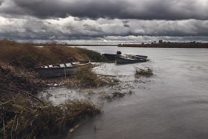Storm clouds over river bank with wooden boats at autumn day.