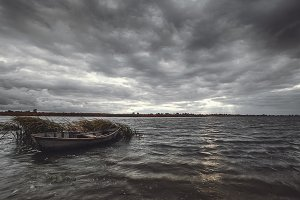Storm clouds over river bank with wooden boat at autumn day.