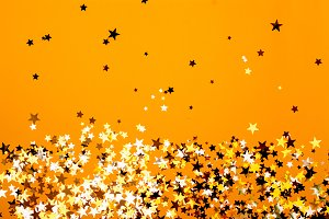 Star shaped confetti on orange paper background