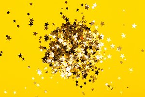 Star shaped confetti on yellow background