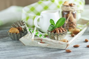 Almonds, mint leaves, jar with milk and different decorations on the wooden tray