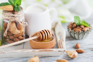 Almonds, honey in the bowl, mint leaves, jar with milk and different decorations