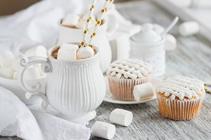 Cups with cacao and marshmallow, cupcakes and different decorations, wooden background