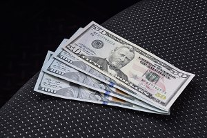 Several banknotes American dollars lie on the car seat. The money in the car
