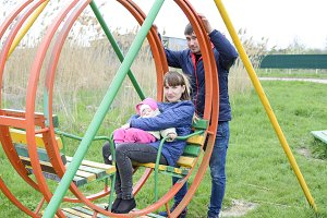 Young married couple with child in playground. Young family on a swing