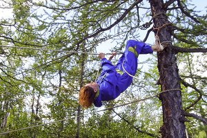 A tourist girl climbs a rope between the trees