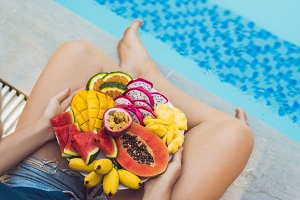 Young woman relaxing and eating fruit plate by the hotel pool. Exotic summer diet. Photo of legs with healthy food by the poolside, top view from above. Tropical beach lifestyle