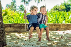 Two little blonde boys having fun on the swing on the tropical sandy coast