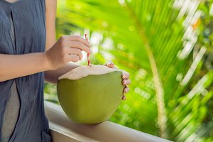 coconut in beautiful female hands on a green background. The Benefits of Coconut Water Concept