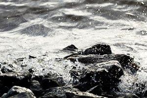 Coastal rocks on wave background