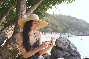 Young sexy woman in swimsuit and hat making selfie shoot using smartphone during vacation on beach