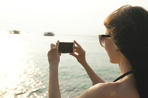 Woman tourist on beach island taking photograph of sunset with smartphone on holiday of boat and skyline view