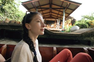 Young woman tourist ride wooden boat in flaoting market in Thailand and watching ethnic people