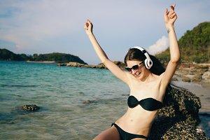 Happy beautiful woman listening to music on wireless headphones on beach near sea
