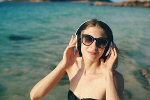 Happy beautiful woman listening to music on wireless headphones on beach near sea