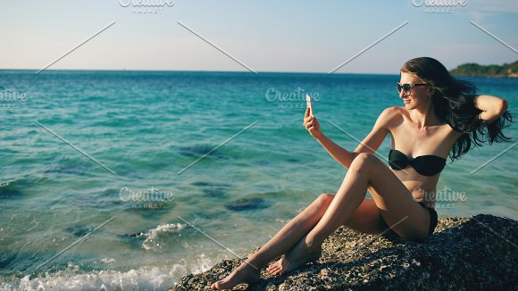 Beautiful woman taking selfie using phone on beach smiling and enjoying traveling lifestyle on vacation