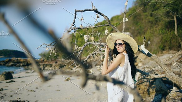 Young sexy woman in sunglasses and hat smiling and posing near tree at beautiful tropical beach in Graphics