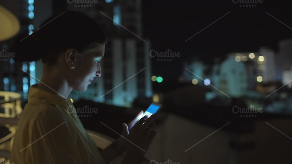 Closeup of young smiling woman texting on smartphone standing on rooftop terrace at night