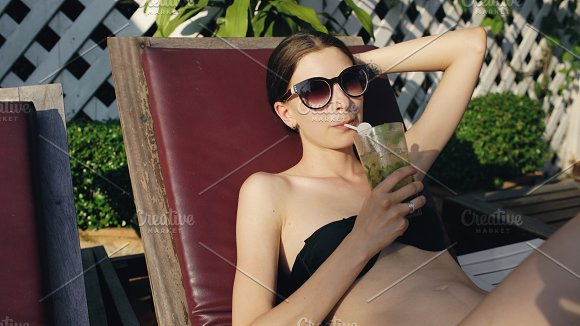 Happy woman sitting by swimming pool in hotel and drinking exotic cocktail in Graphics