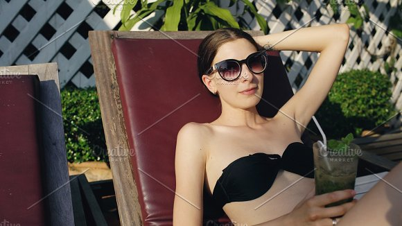 Happy woman sitting by swimming pool in hotel and drinking exotic cocktail