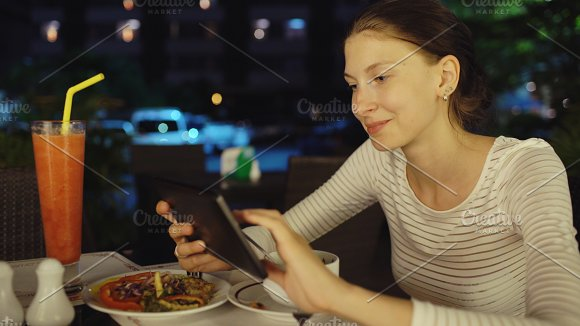Happy woman using smartphone and messaging sitting in restaurant at night