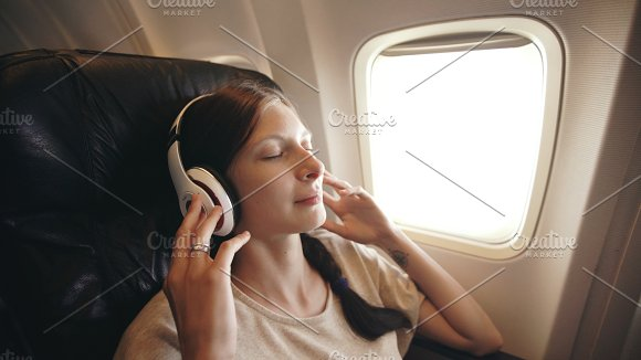 Young woman in wireless headphones listening to music and smiling during fly in airplane in Graphics