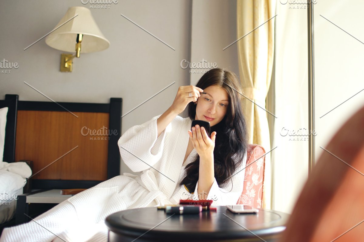 Bathrobe happy woman sitting on chair and making makeup herself in hotel room