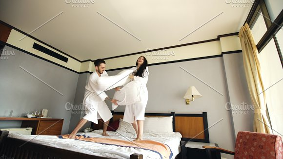 Young happy couple in bathrobe fight pillows and have fun on bed in hotel during their honeymoon vacation in Graphics