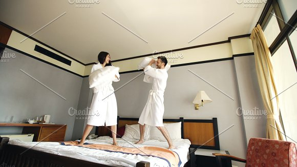 Young happy couple in bathrobe fight pillows and have fun on bed in hotel during their honeymoon vacation